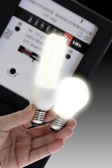 Energiesparlampe und Glühbirne, Stromzähler im Hintergrund