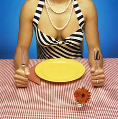 Frau sitzt am Tisch mit leerem Teller vor sich