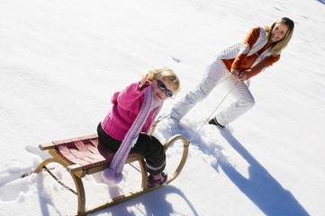 Mädchen sitzt auf Schlitten, die Mutter zieht