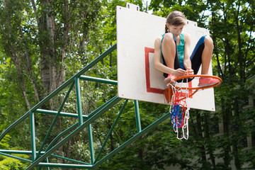 Agile young girl fixing a net on a basketball goal
