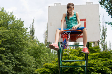 Teenage girl repairing a basketball net