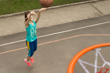 Active young teenage girl playing basketball