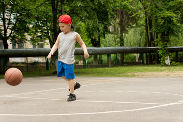 Cute little boy playing basketball