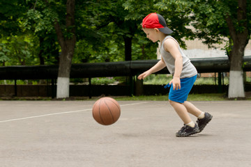 Small boy bouncing a basketball on a court