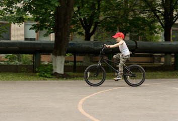 Young boy riding his bike on a basketball court