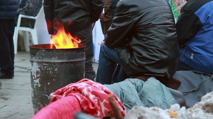 Poor people warming near fire trash barrel, winter outdoors