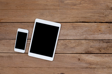 Smartphone and tablet with black screen on old wooden background