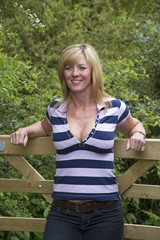 Attractive woman leaning on wooden gate