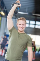 Man lifting kettlebell at crossfit center