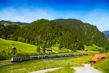 Train crossing countryside near hills, Switzerland