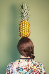 Colorful fashion girl holding pineapple over head