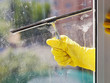 hand in yellow glove cleans window by squeegee