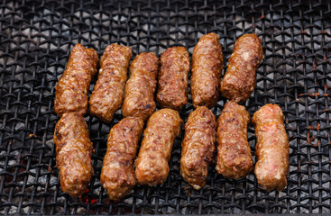 Grilled Romanian meat rolls on barbecue grid - mititei, mici