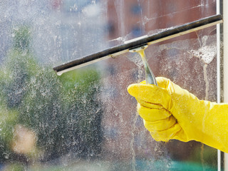 hand in yellow glove wiping window by squeegee