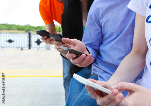 Group of a students chatting with their smartphones