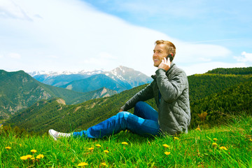 Casual wearing man talking on cellphone outdoor. Mountains