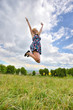 Young girl jumping high in a summer field