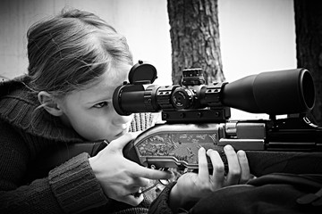 Girl aiming a pneumatic gun