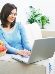 Woman using laptop, working, sitting on couch.