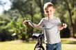 little boy walking with a bike