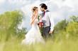 Hochzeit Braut und Bräutigam in Wiese mit Brautstrauß