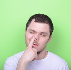 Portrait of a young man with his finger in his nose against gree
