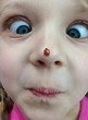 child with ladybird on her nose
