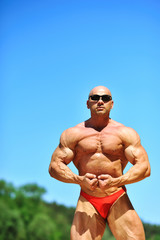 Bodybuilder flexing his muscles outdoors