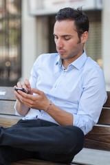 Mann schreibt auf dem Handy
