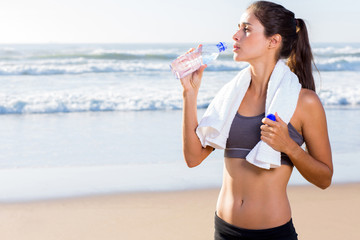 woman drinking water after working out