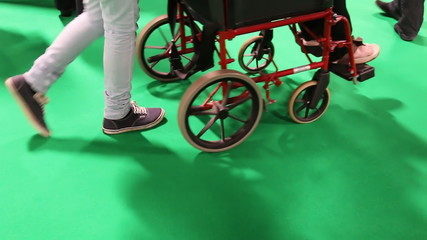 People, caretaker pushing wheelchair on green background
