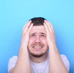 Portrait of sad man looking up against blue background