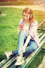 Teenage girl with smart phone and headphones listening music