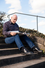 Man sitting on steps reading a newspaper