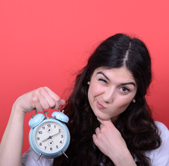 Portrait of girl pointing at clock against red background