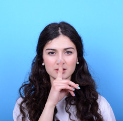 Portrait of girl with gesture for silence against blue backgroun