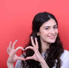 Portrait of happy woman making heart shape with hands against re