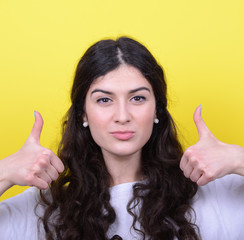 Portrait of happy woman with thumbs up against yellow background