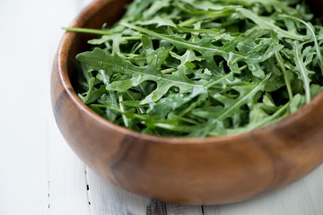 Fresh arugula lettuce in a wooden bowl, horizontal shot