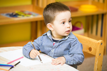 Little child boy drawing with colorful pencils in preschool