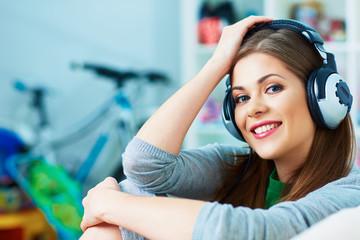 Smiling woman listening music in headphones.