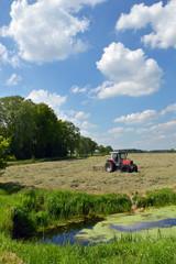 A farm tractor pulling a hay rake in a field