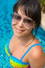 Portrait of a beautiful young woman in the pool