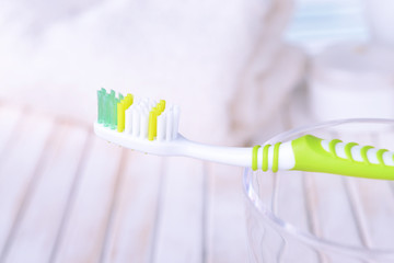 Toothbrush in glass on table on light background