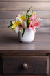 Alstroemeria flowers in vase on table on grey background
