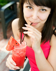 Close up portrait of young smiling woman with the watermelon ju