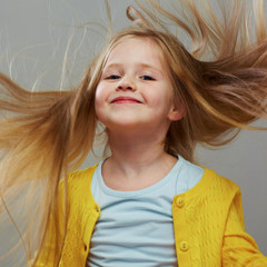 Happy girl child with long blond hair.