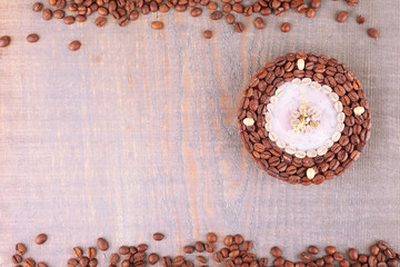 Beautiful clock of coffee beans, on wooden  background