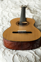 Spanish guitar lying on the bed