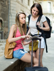 Girls with luggage reading map